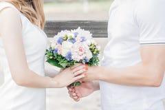 新娘和新郎的手拿着美丽的婚礼花束 免版税库存图片