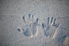 新娘和新郎的指纹与婚戒在海滩的沙子 免版税图库摄影