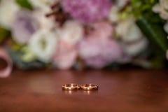 新娘和新郎的经典之作婚礼金戒指的照片图象在一张白色桌上,与花o美丽的婚礼花束  免版税库存照片