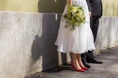 新娘和新郎的脚射击倾斜了对墙壁在一晴朗的婚礼之日 免版税库存照片