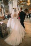 新娘和新郎的长的婚礼礼服的后面看法在仪式期间在教会里 库存图片