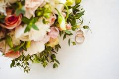新娘和新郎的经典之作婚礼金戒指的照片图象在一张白色桌上 图库摄影