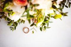 新娘和新郎的经典之作婚礼金戒指的照片图象在一张白色桌上 免版税库存照片