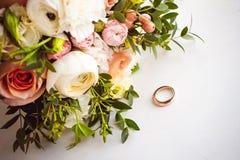 新娘和新郎的经典之作婚礼金戒指的照片图象在一张白色桌上 免版税图库摄影