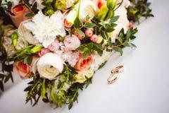 新娘和新郎的经典之作婚礼金戒指的照片图象在一张白色桌上 库存照片