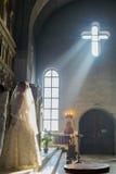 新娘和新郎站立在圣障对面 免版税库存照片