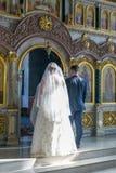 新娘和新郎站立在圣障对面 免版税图库摄影