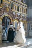 新娘和新郎站立在教士对面在圣障附近 免版税库存照片