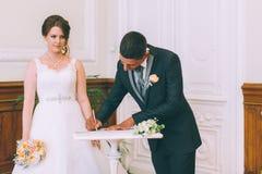 新娘和新郎签署的结婚证书 免版税库存图片