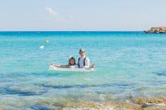 新娘和新郎获得乐趣在含沙热带海滩 免版税库存照片