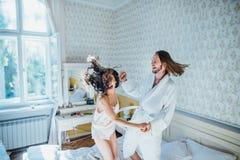 新娘和新郎获得乐趣在床 免版税库存照片