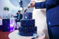 新娘和新郎被切的蓝色婚宴喜饼 库存照片