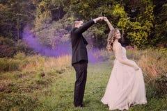 新娘和新郎跳舞在有紫色烟的森林里 免版税图库摄影