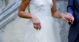 新娘和新郎通过戴着他们的婚戒握手4K 4k 股票视频