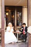 新娘和新郎饮用的咖啡在一个室外咖啡馆 库存照片