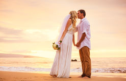 新娘和新郎,享受在一美丽热带的惊人的日落 免版税库存照片