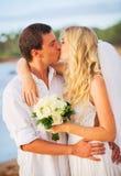 新娘和新郎,亲吻在一个美丽的热带海滩的日落 免版税库存照片