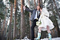 新娘和新郎戴香槟眼镜在冬天森林里 免版税库存照片