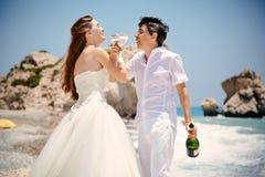 新娘和新郎戴香槟眼镜在海滩地中海 免版税库存照片