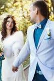 新娘和未婚夫微笑,当一起走在公园附近时 免版税图库摄影