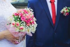 新娘和钮扣眼上插的花新郎的婚礼花束 免版税库存照片