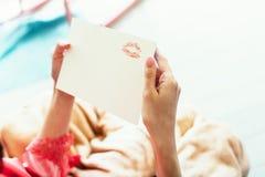 新娘在与红色唇膏的纸做一个亲吻他的新郎的 库存照片