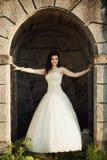 新娘在古老城堡的曲拱站立 免版税库存照片