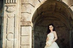 新娘在城堡的石曲拱站立 免版税库存照片