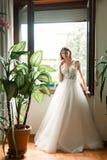 新娘在她的婚礼礼服的一个开窗口附近站立 库存照片