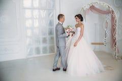 新娘在她的手上拥抱新郎并且拿着花花束  新婚佳偶一对美好的夫妇在一婚礼之日 免版税库存照片