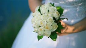 新娘在她的手上拿着大美丽的婚姻的花束,接触在它的花,指法他们与她