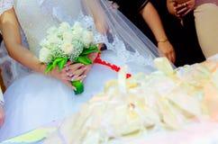 新娘在她的手上拿着白色玫瑰花束 新娘的花花束  新娘拿着花婚礼花束  免版税库存图片