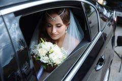 新娘在婚礼礼服和面纱打扮,她的头在汽车装饰与翻领并且坐并且敬佩 库存图片
