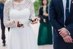 新娘在手上拿着一只蝴蝶 免版税库存图片