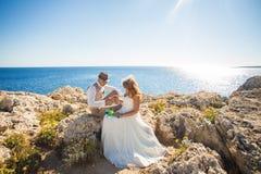 新娘在新郎` s手指上把圆环放 在海滩的婚礼夫妇 免版税库存图片