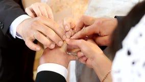新娘在新郎` s手指的穿戴圆环 有圆环的婚姻手 birde戴着在新郎的手指的圆环 影视素材