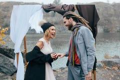 新娘在新郎` s手指,愉快和快乐的片刻投入婚戒 秋天户外婚礼 免版税库存照片