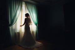 新娘在用绿色帷幕盖的窗口前站立 库存照片
