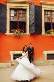 新娘在站立在橙色房子后的新郎前旋转 免版税库存图片