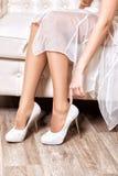 新娘在脚上把白色鞋子放 免版税库存图片