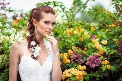 新娘在花包围的一个繁茂花园里 免版税库存照片