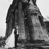 新娘在主教的座位附近拥抱一个新郎从与他的后面身分 库存照片