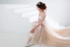 新娘坐台阶 一个美丽的女孩的画象婚礼礼服的 跳舞新娘,白色背景 免版税库存照片