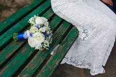 新娘坐长凳在婚礼花束旁边 免版税库存照片