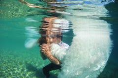 新娘夫妇亲吻的水中 免版税库存照片