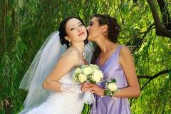 新娘女孩亲吻年轻人 免版税图库摄影