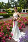 新娘她的白色婚礼礼服的和有花花束的  库存照片