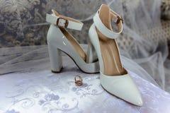 新娘婚姻的鞋子和圆环在白色背景 免版税库存照片