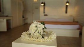 新娘婚礼花束和夏威夷列伊在屋子里缠绕做白色兰花在桌 没有人民 在滑子的照相机 股票录像