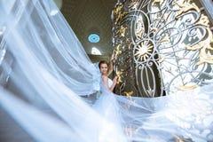 新娘婚装的秀丽新娘有在自然的花束和鞋带面纱的 免版税图库摄影